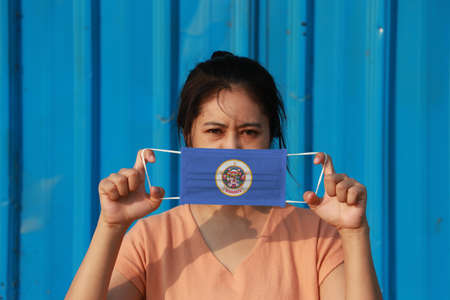 A woman and hygienic mask with Minesota flag pattern in her hand and raises it to cover her face. A mask is a very good protection from Tiny Particle or virus corona or Covid 19. Archivio Fotografico - 158053142