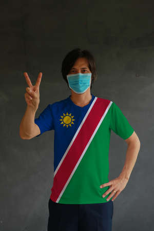 Man wearing hygienic mask and wearing Namibian flag colored shirt and raising two fingers up on dark wall background. Concept of protect tiny dust or disease of Namibia. Archivio Fotografico - 158053138