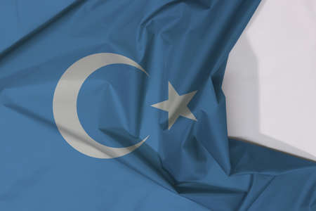 Uyghuristan fabric flag crepe and crease with white space, a blue field with a white crescent moon and five pointed star slightly left of centre. Archivio Fotografico