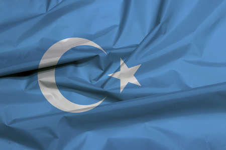 Fabric flag of East Turkestan. Crease of Uyghuristan flag background, a blue field with a white crescent moon and five pointed star slightly left of centre.