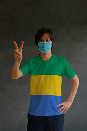 Man wearing hygienic mask and wearing Gabonese flag colored shirt and raising two fingers up on dark wall background. Concept of protect tiny dust or disease of Gabon.