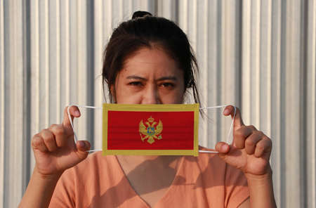 A woman with Montenegro flag on hygienic mask in her hand and lifted up the front face on grey background. Tiny Particle or virus corona or Covid 19 protection. Concept of Combating illness. Archivio Fotografico - 158168920