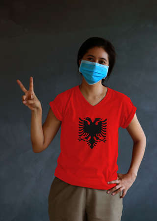 Woman wearing hygienic mask and wearing Albanian flag colored shirt and raising two fingers up on dark wall background. Concept of protect tiny dust or disease of Albania. Archivio Fotografico