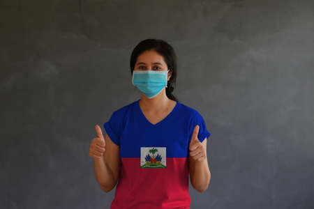 Woman wearing hygienic mask and wearing Haiti flag colored shirt with thumbs up with both hands on dark wall background. Concept of protect tiny dust or disease.