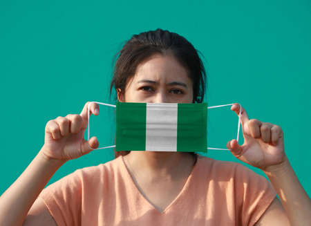 A woman with Nigeria flag on hygienic mask in her hand and lifted up the front face on green background. Tiny Particle or virus corona or Covid 19 protection. Concept of Combating illness. Archivio Fotografico