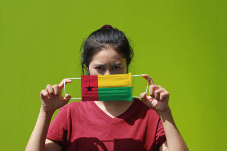 A woman and hygienic mask with Guinea Bissau flag pattern in her hand and raises it to cover her face on green background. A mask is a very good protection from Tiny Particle or respiratory disease.