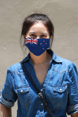 New Zealand flag on hygienic mask. Masked woman prevent germs and wear denim dress. Tiny Particle or respiratory disease protection. Concept of Combating illness. Archivio Fotografico