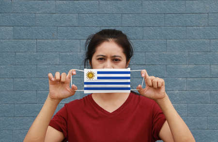 A woman and hygienic mask with Uruguay flag pattern in her hand and raises it to cover her face on blue wall background. A mask is a very good protection from Tiny Particle or respiratory disease.