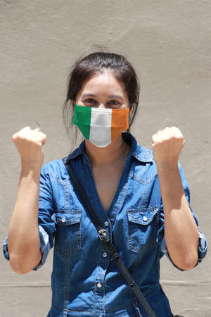 Ireland flag on hygienic mask. Masked woman prevent germs and wear denim dress. Tiny Particle or respiratory disease protection. Concept of Combating illness.