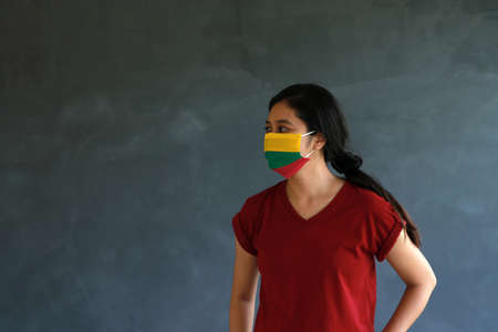 Woman wearing Lithuania flag colored hygienic mask with brown shirt and facing to the side on dark wall background. Concept of protect tiny dust or disease. Archivio Fotografico