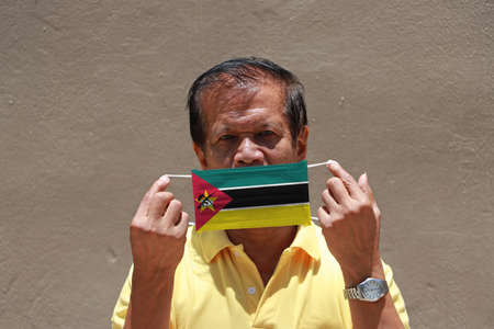 A man and hygienic mask with Mozambique flag pattern in his hand and raises it to cover his face. A mask is a very good protection from Tiny Particle or respiratory disease.