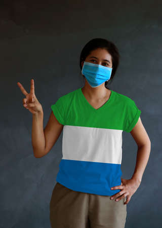 Woman wearing hygienic mask and wearing Sierra Leone flag colored shirt and raising two fingers up on dark wall background. Concept of protect tiny dust or disease.