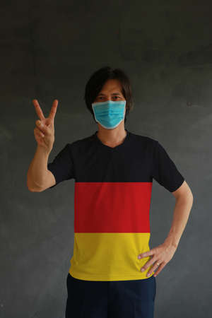 Man wearing hygienic mask and wearing German flag colored shirt and raising two fingers up on dark wall background. Concept of protect tiny dust or disease of Germany. Archivio Fotografico - 158308049