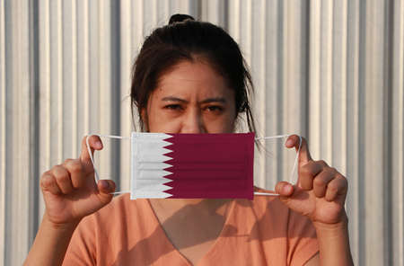 A woman with Qatar flag on hygienic mask in her hand and lifted up the front face on grey background. Tiny Particle or virus corona or Covid 19 protection. Concept of Combating illness. Archivio Fotografico - 158308051