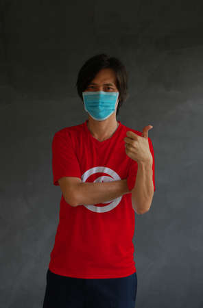 Man wearing hygienic mask and wearing Tunisia flag colored shirt and cross one s arm with thumbs up on dark wall background. Concept of protect tiny dust or disease.