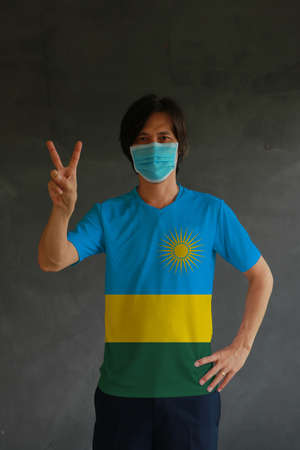 Man wearing hygienic mask and wearing Rwanda flag colored shirt and raising two fingers up on dark wall background. Concept of protect tiny dust or disease. Archivio Fotografico