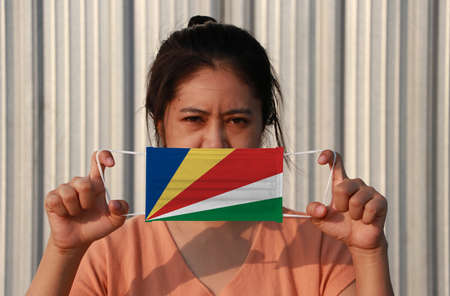 A woman with Seychelles flag on hygienic mask in her hand and lifted up the front face on grey background. Tiny Particle or virus corona or Covid 19 protection. Concept of Combating illness. Archivio Fotografico - 158410033