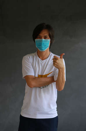 Man wearing hygienic mask and wearing Cyprus flag colored shirt and cross one s arm with thumbs up on dark wall background. Concept of protect tiny dust or disease.