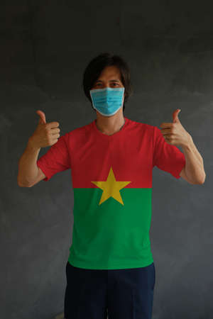 Man wearing hygienic mask and wearing Burkina faso flag colored shirt with thumbs up on both hands. Concept of protect tiny dust or disease.