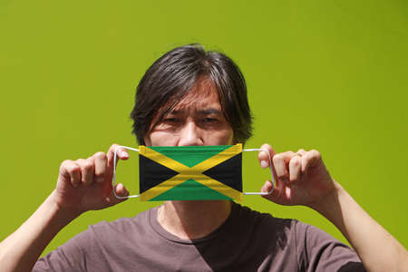 A man and hygienic mask with Jamaica flag pattern in his hand and raises it to cover his face on green background. A mask is a very good protection from Tiny Particle or respiratory disease.