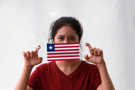 A woman and hygienic mask with Liberia flag pattern in her hand and raises it to cover her face on white background. A mask is a very good protection from Tiny Particle or respiratory disease. Archivio Fotografico