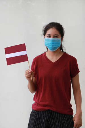 Masked woman in brown shirt and Latvia flag in hand. Concept of living a new way to prevent epidemics. Archivio Fotografico