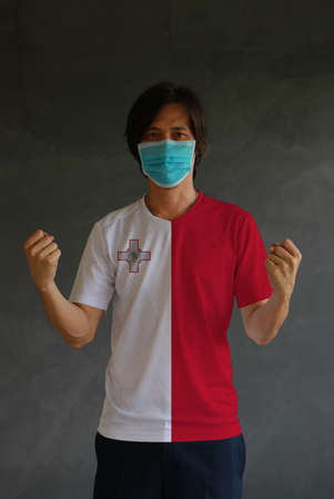 Man wearing hygienic mask and wearing Malta flag colored shirt and standing with raised both fist on dark wall background. Concept of protect tiny dust or disease.