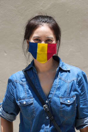 Chad flag on hygienic mask. Masked woman prevent germs and wear denim dress. Tiny Particle or respiratory disease protection. Concept of Combating illness. Archivio Fotografico