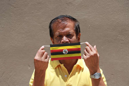 A man and hygienic mask with Uganda flag pattern in his hand and raises it to cover his face. A mask is a very good protection from Tiny Particle or respiratory disease.
