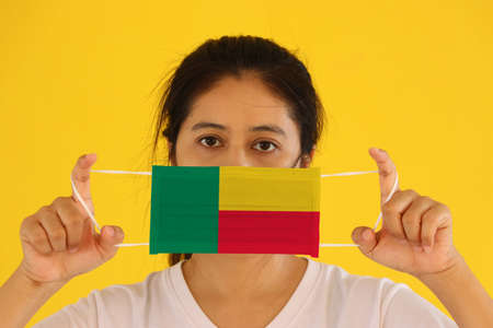 A woman in white shirt with Benin flag on hygienic mask in her hand and lifted up the front face on yellow background. Tiny Particle or virus corona or Covid 19 protection. Concept of Combating illness. Archivio Fotografico