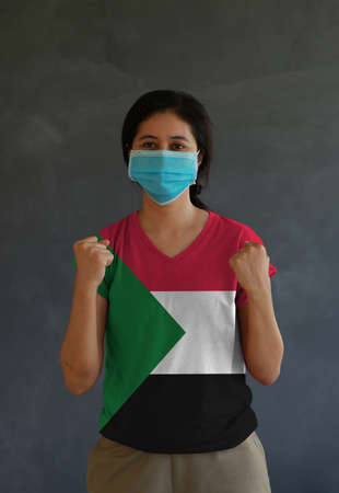Woman wearing hygienic mask and wearing Sudanese flag colored shirt and standing with raised both fist on dark wall background. Concept of protect tiny dust or disease of Sudan.