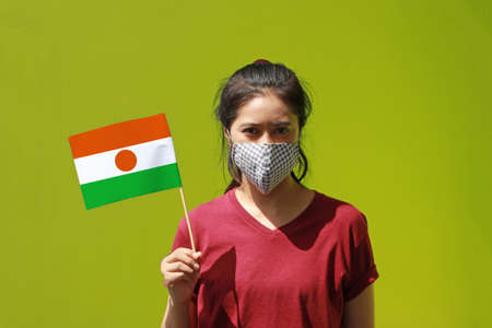 Masked woman in brown shirt and Niger flag in hand on green background. Concept of living a new way to prevent epidemics. Archivio Fotografico