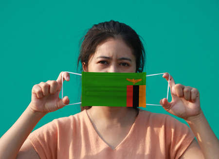 A woman with Zambia flag on hygienic mask in her hand and lifted up the front face on green background. Tiny Particle or virus corona or Covid 19 protection. Concept of Combating illness. Archivio Fotografico