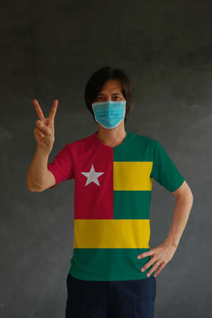 Man wearing hygienic mask and wearing Togo flag colored shirt and raising two fingers up on dark wall background. Concept of protect tiny dust or disease.