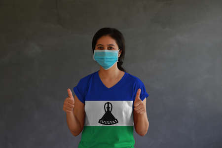 Woman wearing hygienic mask and wearing Lesotho flag colored shirt with thumbs up on both hands. Concept of protect tiny dust or disease. Archivio Fotografico