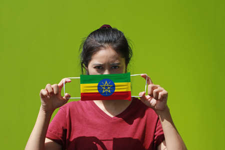 A woman and hygienic mask with Ethiopia flag pattern in her hand and raises it to cover her face on green background. A mask is a very good protection from Tiny Particle or respiratory disease. Archivio Fotografico