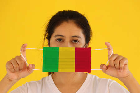 A woman in white shirt with Mali flag on hygienic mask in her hand and lifted up the front face on yellow background. Tiny Particle or virus corona or Covid 19 protection. Concept of Combating illness.