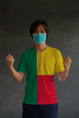 Man wearing hygienic mask and wearing Benin flag colored shirt and standing with raised both fist on dark wall background. Concept of protect tiny dust or disease.