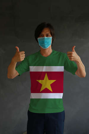 Man wearing hygienic mask and wearing Suriname flag colored shirt with thumbs up on both hands. Concept of protect tiny dust or disease.