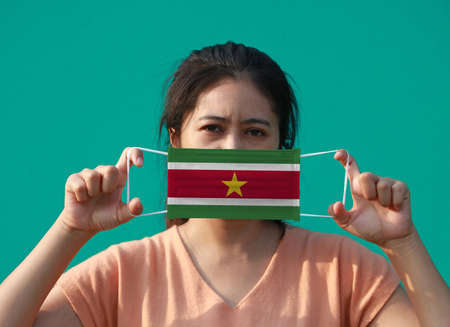 A woman with Suriname flag on hygienic mask in her hand and lifted up the front face on green background. Tiny Particle or virus corona or Covid 19 protection. Concept of Combating illness. Archivio Fotografico
