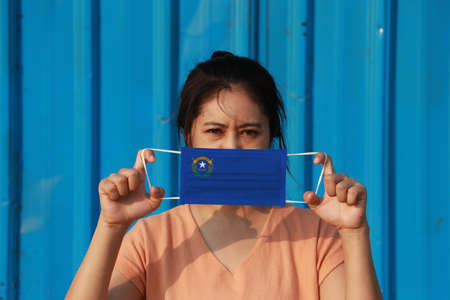 A woman and hygienic mask with Nevada flag pattern in her hand and raises it to cover her face on blue background. A mask is a very good protection from Tiny Particle or virus corona or Covid 19.