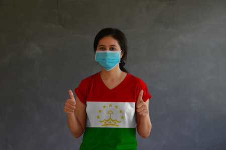Woman wearing hygienic mask and wearing Tajiks flag colored shirt with thumbs up with both hands on dark wall background. Concept of protect tiny dust or disease of Tajikistan.