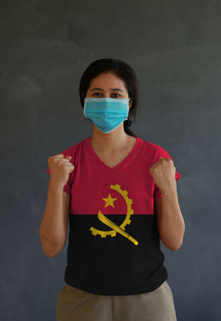 Woman wearing hygienic mask and wearing Angola flag colored shirt and standing with raised both fist on dark wall background. Concept of protect tiny dust or disease.