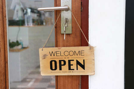 Open sign hung on the door. welcome customers to enter the shop. Archivio Fotografico