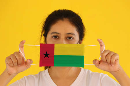 A woman in white shirt with Guinea bissau flag on hygienic mask in her hand and lifted up the front face on yellow background.