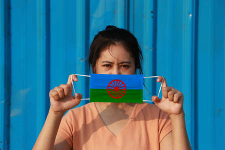 A woman with Romani people flag on hygienic mask in her hand and lifted up the front face on blue background.