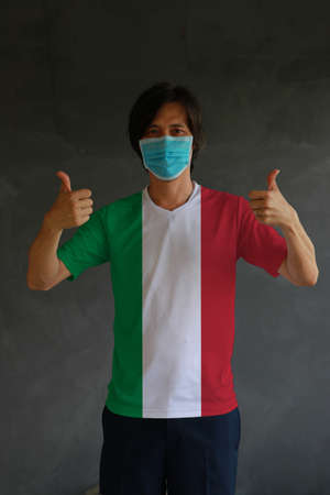 Man wearing mask to prevent epidemic and wearing Italian flag colored shirt with thumbs up on both hands.