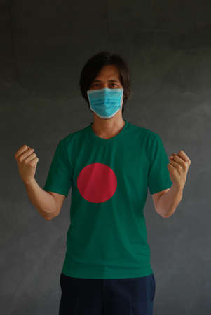 Man wearing hygienic mask and wearing Bangladesh flag colored shirt and standing with raised both fist on dark wall background.