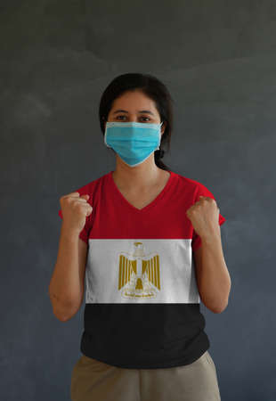 Woman wearing hygienic mask and wearing Egypt flag colored shirt and standing with raised both fist on dark wall background.