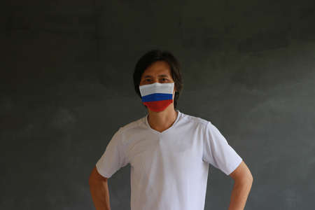 Masked man prevent germs with Russia flag pattern mask and wear white shirt. Tiny Particle or virus corona or Covid 19 protection. Archivio Fotografico